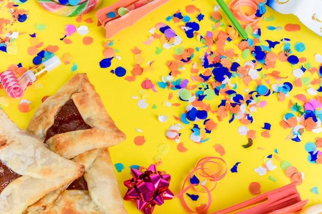 Purim-hintergrund mit partykostüm- und hamantaschen-plätzchen