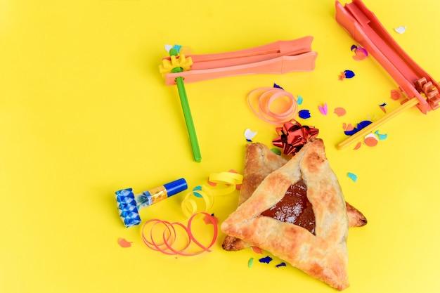 Purim hintergrund mit partykostüm und hamantaschenplätzchen