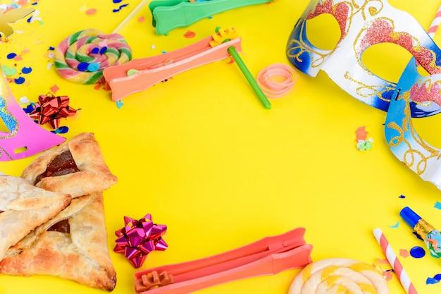 Purim mit karnevalsmaske, partykostüm und hamantaschen