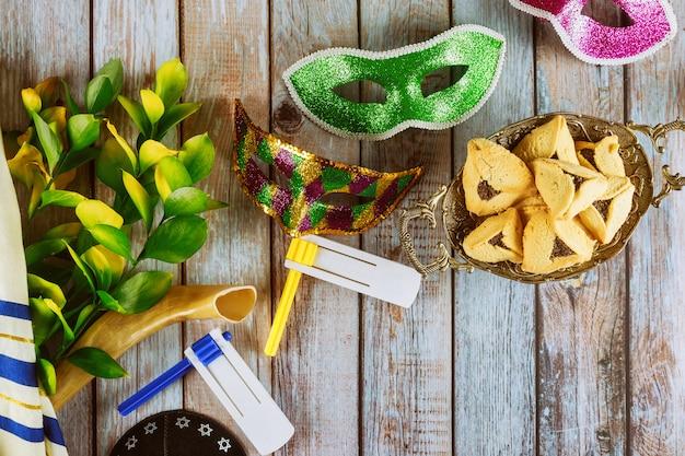 Purim urlaub mit keksen hamans ohren in eimer karnevalsmaske über rustikalem hintergrund