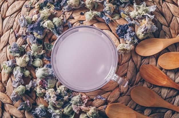 Purpurfarbenes wasser der draufsicht auf untersetzerhintergrund mit teekräutern und löffeln horizontal