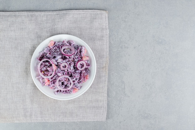 Purpurkohl-zwiebel-salat mit verschiedenen zutaten in keramikbechern.