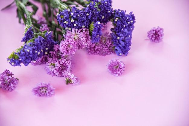 Purpurrote blume marguerite und statice blumen des neuen frühlinges gestalten zusammensetzungsanlage auf purpurrotem weichem rosa