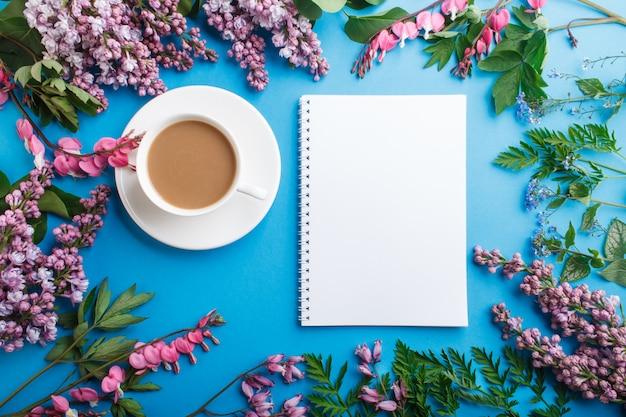 Purpurrote blumen der flieder und des blutenden herzens und ein tasse kaffee mit notizbuch