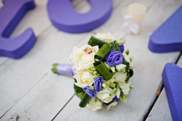 Purpurrote dekorhochzeitswortliebe mit blumenstrauß und ringen