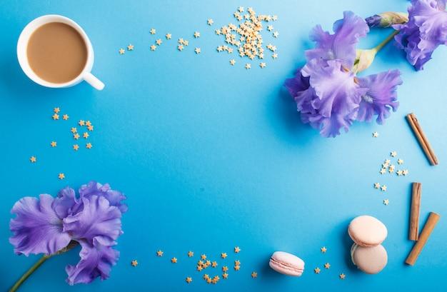 Purpurrote irisblumen und ein tasse kaffee auf blauem pastell