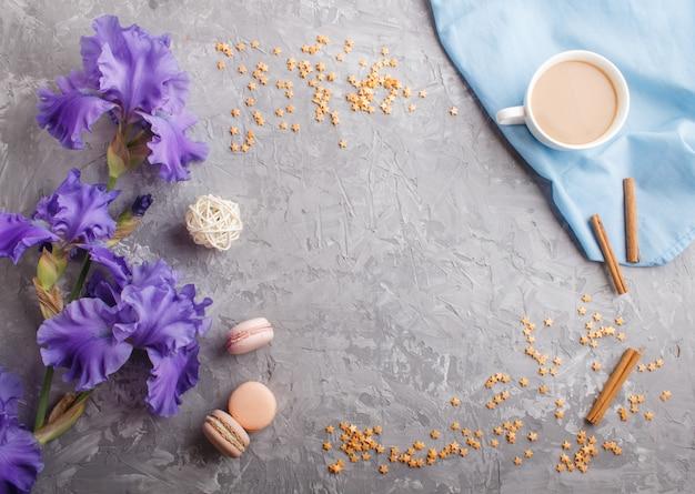 Purpurrote irisblumen und ein tasse kaffee auf grauem beton