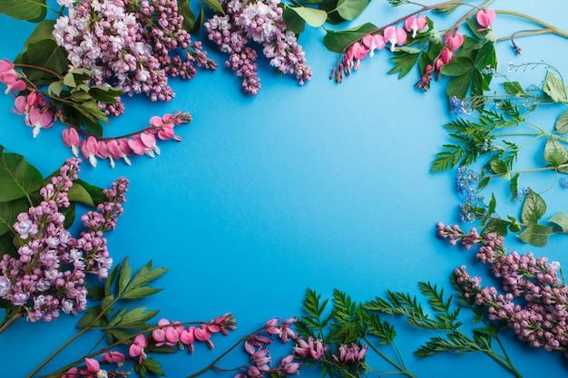 Purpurrote lila und blutende herzblumen auf blauem pastellhintergrund.