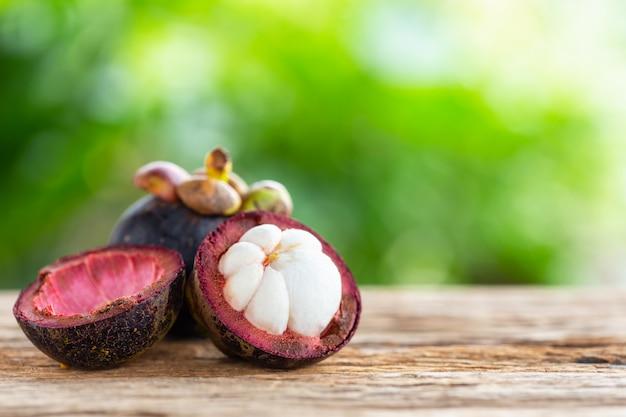 Purpurrote mangostanfruchtfrucht auf holztischhintergrund mit grünem unschärfelichtraumhintergrund