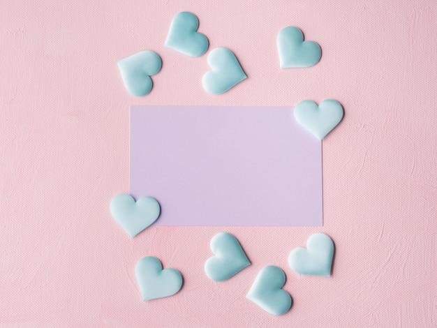 Purpurrote pastellkarte und herzen auf dem rosa gemasert