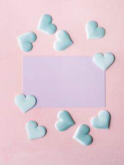Purpurrote pastellkarte und herzen auf rosa strukturiertem hintergrund