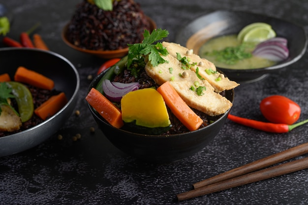 Purpurrote reisbeeren gekocht mit gegrillter hühnerbrust. kürbis, karotten und minze in einer schüssel, sauberes essen.