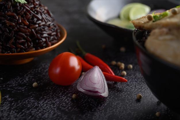 Purpurrote reisbeeren in einer schüssel mit roten zwiebeln, paprikas und tomaten