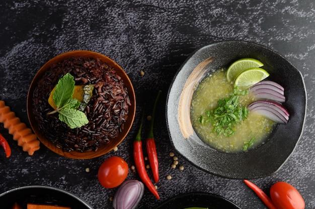Purpurrote reisbeeren mit kürbis und tadellosen blättern in einer schüssel und in einer suppe