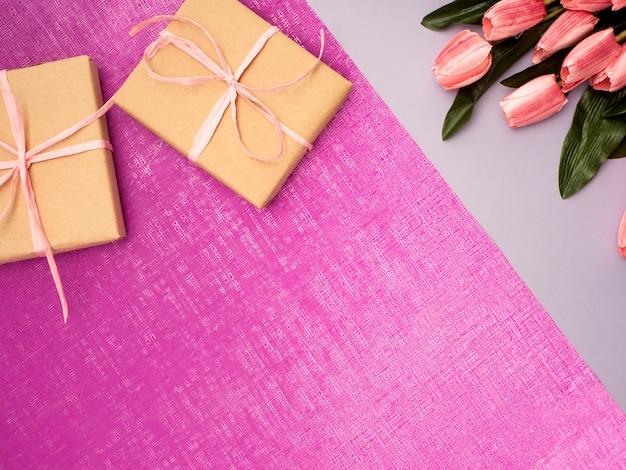 Purpurrote tulpe und geschenkbox auf purpurrotem hintergrund
