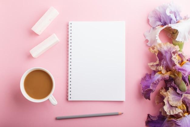 Purpurrote und blaue irisblumen und ein tasse kaffee mit leerem notizbuch