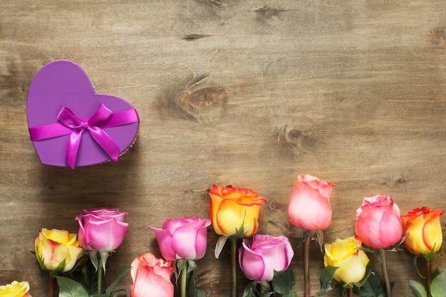 Purpurrote und gelbe rosen, kasten vorhanden auf hölzernem hintergrund