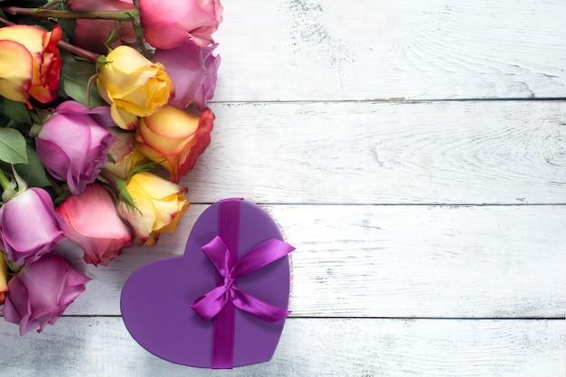 Purpurrote und gelbe rosen, kasten vorhanden auf weißem hölzernem hintergrund