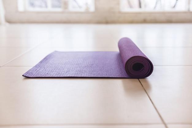 Purpurrote yogamatte, die auf dem hellen boden liegt