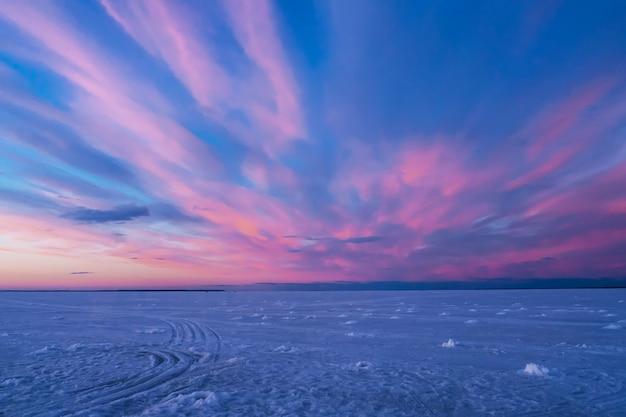 Purpurroter blauer sonnenuntergang oder sonnenaufgang im winter über dem fluss