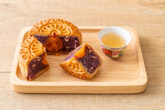 Purpurroter süßkartoffelgeschmack des chinesischen mondkuchens mit tee auf holzteller