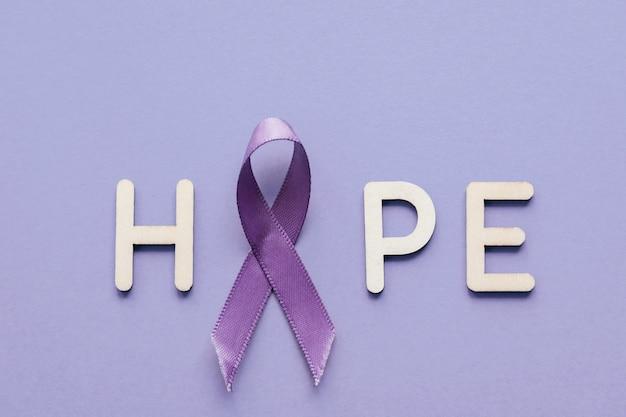 Purpurrotes band mit hölzernem buchstaben der hoffnung auf purpurrotem hintergrund