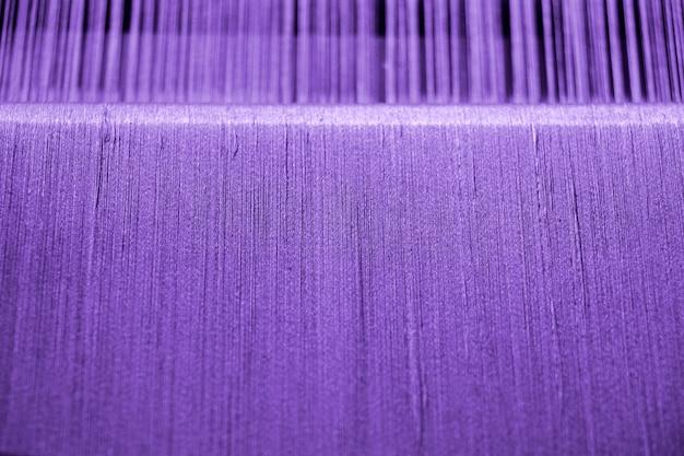 Purpurrotes baumwollgarn auf webstuhl für handwerksbeschaffenheitshintergrund