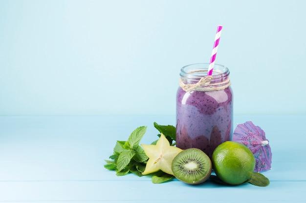 Purpurrotes smoothieglas auf blauem hintergrund