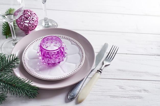 Purpurrotes weihnachtsgedeck mit kerzenständer und gläsern wein über hellem fenster