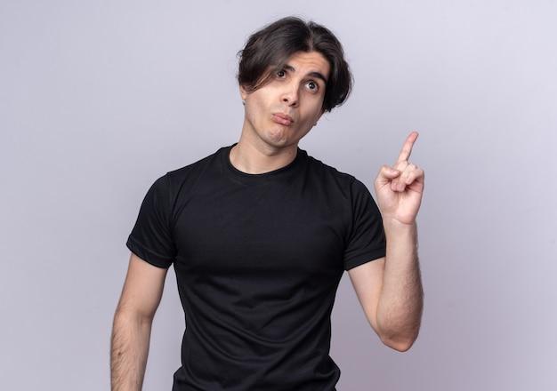 Pursing lippen junger hübscher kerl, der schwarzes t-shirt trägt, zeigt oben oben auf weißer wand