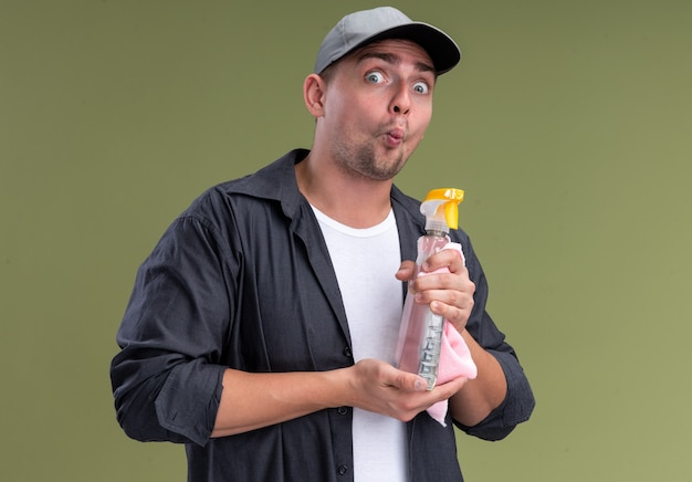 Pursing lippen junger hübscher reinigungsmann, der t-shirt und kappe hält lappen mit sprühflasche lokalisiert auf olivgrüner wand