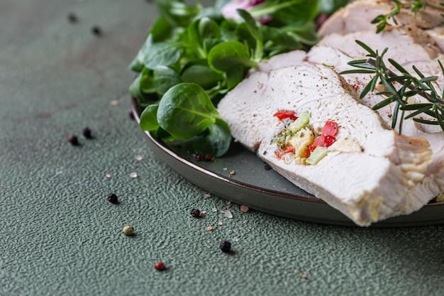 Putenbrust gefüllt mit gemüse und käse mit grünem salat und aromatischen kräutern