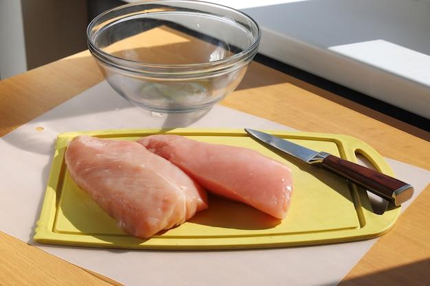 Putenfiletfleisch auf schneidebrett und messer auf tischoberfläche