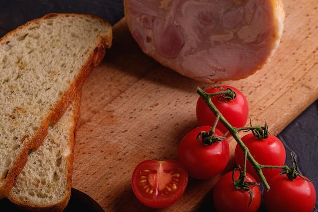 Putenschinkenfleisch, frischer kirschtomatenzweig und geschnittenes brot auf holzschneidebrett.