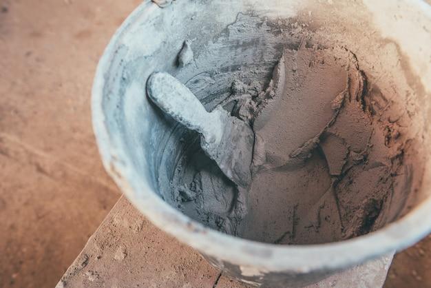 Putz im eimer mit spachtel zur wandrenovierung.