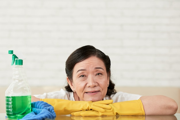 Putzfrau, die auf ihren händen in den handschuhen machen pause vom polieren der tabelle sich lehnt
