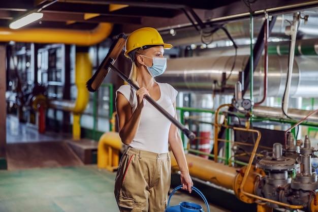 Putzfrau in arbeitskleidung mit schützender gesichtsmaske, die besen und eimer beim gehen in der heizanlage während des ausbruchs des koronavirus hält.