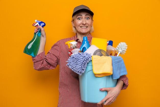 Putzfrau in kariertem hemd und mütze, die eine flasche reinigungsmittel und einen eimer mit reinigungswerkzeugen hält, die glücklich und überrascht aussehen