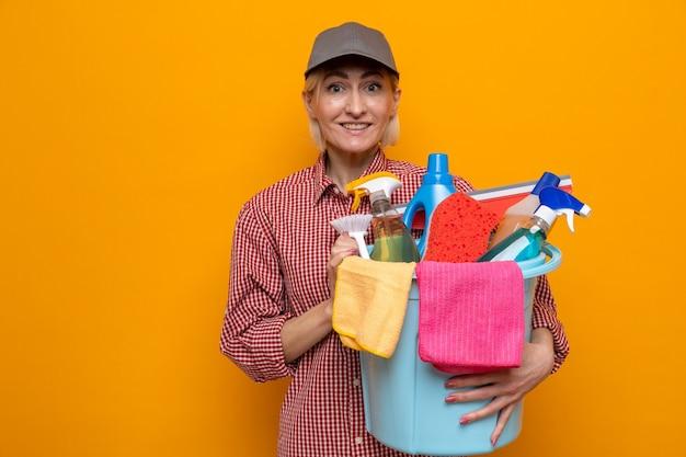 Putzfrau in kariertem hemd und mütze, die einen eimer mit reinigungswerkzeugen hält und die kamera mit einem lächeln auf einem glücklichen gesicht auf orangefarbenem hintergrund anschaut