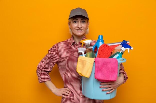 Putzfrau in kariertem hemd und mütze, die einen eimer mit reinigungswerkzeugen hält und die kamera mit einem lächeln im gesicht ansieht, bereit für die reinigung auf orangefarbenem hintergrund