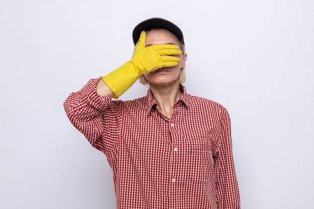 Putzfrau in kariertem hemd und mütze mit gummihandschuhen, die die augen mit der hand bedecken Premium Fotos