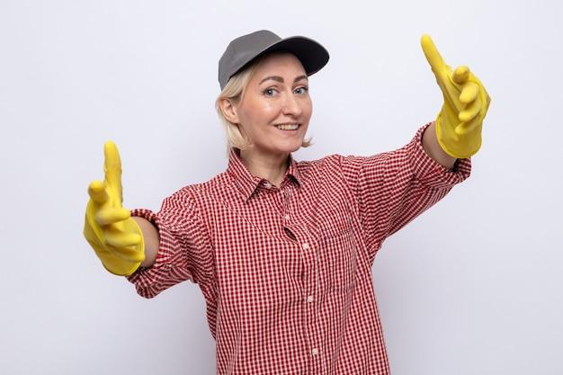 Putzfrau in kariertem hemd und mütze mit gummihandschuhen, die freundlich lächelnd aussieht und eine einladende geste mit den händen macht