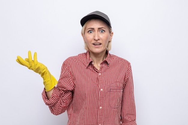 Putzfrau in kariertem hemd und mütze mit gummihandschuhen, die unzufrieden mit ausgestrecktem arm aussieht