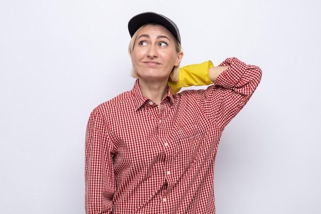 Putzfrau in kariertem hemd und mütze mit gummihandschuhen, die verwirrt aufschaut