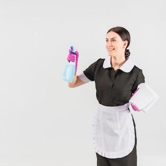 Putzfrau in uniform mit reinigungsmittel und staubtuch