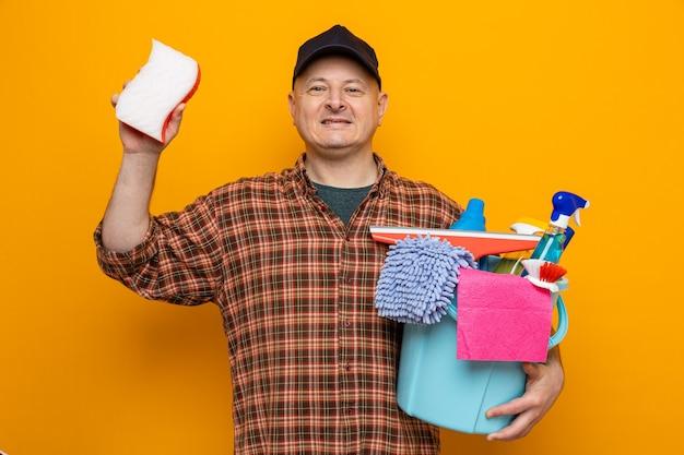 Putzmann in kariertem hemd und mütze mit eimer mit reinigungswerkzeugen und schwamm, der mit einem lächeln im gesicht aussieht