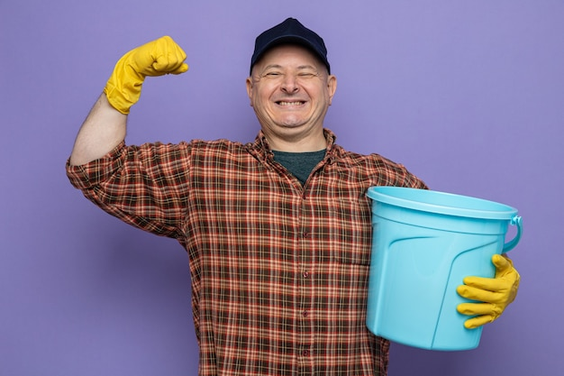 Putzmann in kariertem hemd und mütze mit gummihandschuhen, die einen eimer halten und die faust glücklich und aufgeregt wie ein gewinner auf violettem hintergrund heben