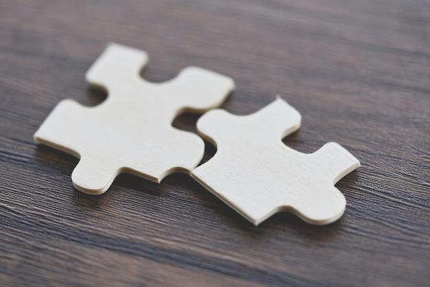 Puzzle auf hölzerner draufsicht - verbindung mit zwei puzzlestücken