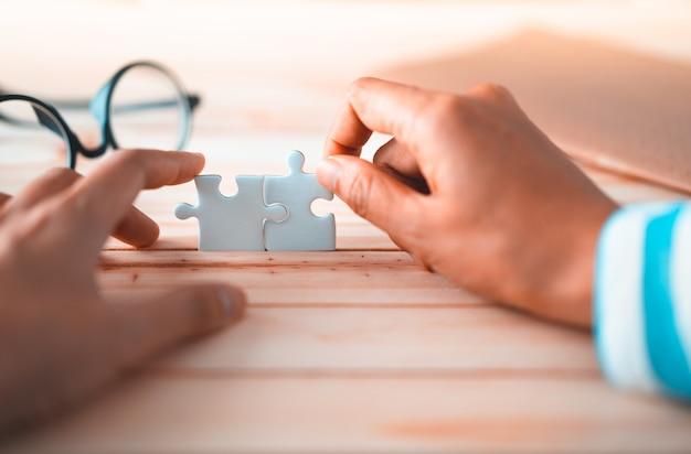 Puzzle, das durch zwei hände, lösung zum erfolgskonzept anschließt