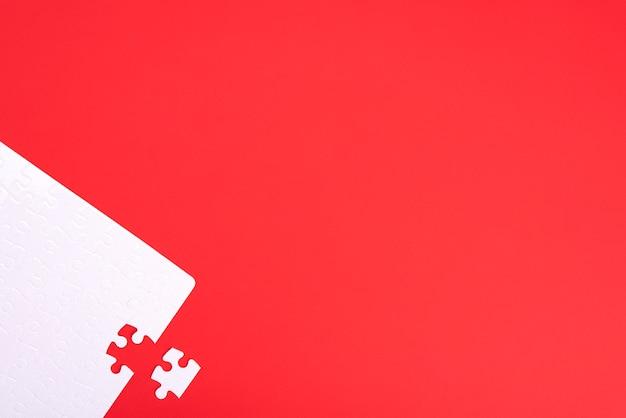 Puzzle der weißen stücke auf rotem hintergrund mit platz für ihren text